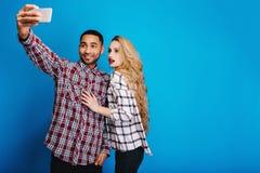 Type beau élégant faisant le portrait de selfie avec la jeune femme attirante avec de longs cheveux blonds sur le fond bleu ayant photo libre de droits