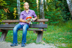 Type beau avec le bouquet attendant son girlfrie Photographie stock