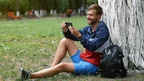 Type beau ayant le smartphone visuel de participation de causerie tout en se reposant sous l'arbre dans le parc Webcam causant à  banque de vidéos
