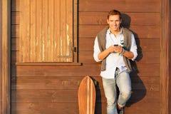 Type beau dans l'équipement quatre-saisons se tenant sur le fond en bois brun et tenant son smartphone - le sourire des hommes en Images stock