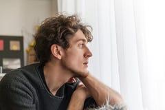 Type beau de jeune homme observant par l'attente de douleur de peine de tristesse de concept de fenêtre photos stock