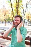 Type beau drôle avec des écouteurs sur la nature image stock