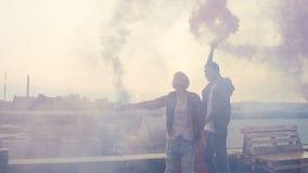 Type beau et belle fille ayant l'amusement avec de la fumée colorée sur le toit du bâtiment moderne Jeune type avec le sien banque de vidéos