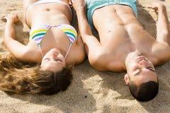 Type beau et son amie s'étendant sur le sable Photos stock