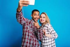 Type beau joyeux faisant le portrait de selfie avec la jolie jeune femme blonde sur le fond bleu Avoir l'amusement, à la mode photographie stock libre de droits