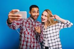 Type beau ?l?gant faisant le portrait de selfie avec la jeune femme attirante avec de longs cheveux blonds sur le fond bleu ayant photos stock