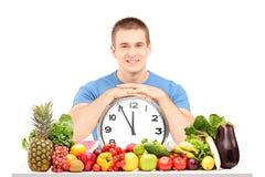 Type beau tenant une horloge murale, posée sur une table Images libres de droits