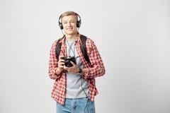 Type blond dans des écouteurs, avec le sac à dos noir sur son épaule habillée dans un T-shirt blanc, une chemise à carreaux rouge images stock