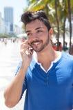 Type brésilien avec le téléphone portable chez Aveniada Atlantica chez Rio de Janeiro Photo stock