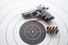 Type of .45 bullets on  bullseye target with blurred pistol Royalty Free Stock Photography