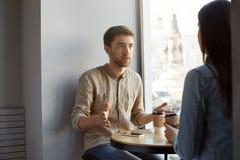 Type caucasien attirant avec les cheveux foncés et poil se reposant en café une date parlant à son amie au sujet de son travail Images libres de droits
