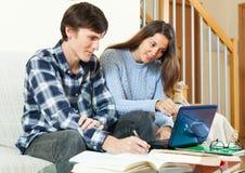Type d'étudiant avec la fille se préparant à la session avec le livre électronique Image libre de droits
