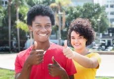 Type d'afro-américain avec l'amie caucasienne montrant le pouce Photo libre de droits