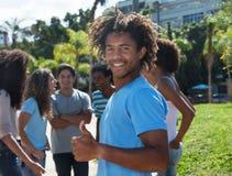 Type d'afro-américain avec la coiffure étonnante et amis montrant le pouce Photographie stock