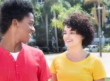 Type d'afro-américain parlant avec l'amie caucasienne Photographie stock libre de droits