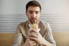 Type d'une chevelure foncé attirant s'asseyant en café, regardant avec l'expression heureuse le sandwich, étant heureux de manger photographie stock