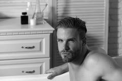 Type dans la salle de bains avec des articles de toilette sur le fond images libres de droits