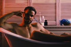 Type dans la salle de bains avec des articles de toilette sur le fond, foyer sélectif Sexe et concept d'art érotique : se reposer image libre de droits