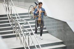 Type dans la veste de denim descendant les escaliers tenant une bicyclette orange Étudiant avec le vélo Images libres de droits