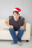 Type dans le capuchon de Noël ayant le regard fixe avec le oeil écarquiller Photographie stock