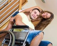 Type dans le fauteuil roulant jouant avec l'ami Photos libres de droits