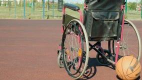 Type de fauteuil roulant avec une boule de panier sur une cour de volleyball de sports Image libre de droits