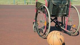 Type de fauteuil roulant avec une boule de panier sur une cour de volleyball de sports Photographie stock libre de droits