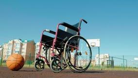 Type de fauteuil roulant avec une boule de panier sur une cour de volleyball de sports Photos libres de droits