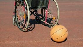 Type de fauteuil roulant avec une boule de panier sur une cour de volleyball de sports Photographie stock