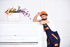 Type de froncement de sourcils avec la moustache élégante soulevant son sourcil Moteur se penchant sur le piano blanc avec peu de Image libre de droits