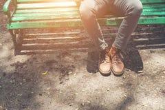 Type de hippie s'asseyant sur le banc avec des jeans et des chaussures brunes de chamois Photographie stock