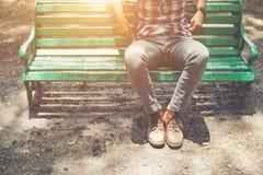 Type de hippie s'asseyant sur le banc avec des jeans et des chaussures brunes de chamois Photo stock