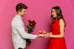 Type de sourire avec les roses rouges faisant un présent pour son amie magnifique Images stock