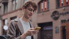 Type de sourire heureux de hippie avec des verres causant avec des amis aux réseaux sociaux et écouter musique, utilisant moderne banque de vidéos