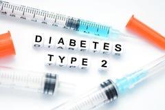 Type - 2 diabetestekst met plastic die brievenparels wordt gespeld naast een insulinespuit die worden geplaatst Stock Afbeeldingen