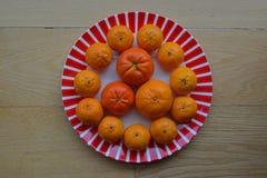 Type différent de mandarines d'un plat rouge de rayures sur le fond en bois Photo stock