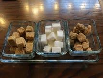 Type différent de sucre de cube blanc et cru sur le fond foncé photographie stock