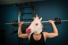 Type drôle dans le masque comique faisant l'exercice de sport images libres de droits