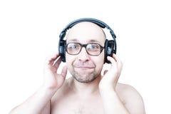 Type drôle avec des écouteurs d'isolement sur le blanc Photo stock