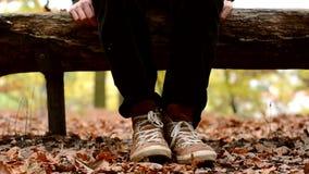 Type ennuyé nerveux sur un banc en parc d'automne banque de vidéos