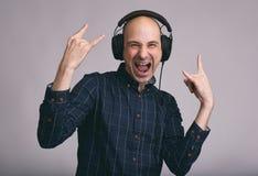 Type enthousiaste écoutant la musique avec des écouteurs Images libres de droits