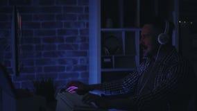Type enthousiaste dans des écouteurs jouant le jeu vidéo d'ordinateur à la maison tard la nuit banque de vidéos