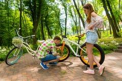 Type essayant de fixer un vélo tandis que son amie surveille le proce Images libres de droits