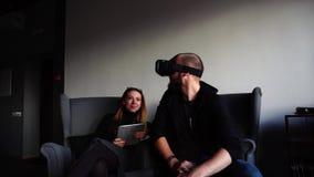 Type et amie avec les instruments et l'homme en verres de VR, s'asseyent dans des fauteuils dans le café moderne et la causerie d