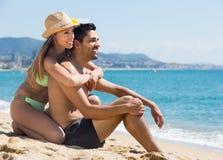 Type et amie se reposant sur la plage sablonneuse Photographie stock libre de droits