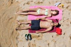 Type et amie se reposant sur le sable Photo libre de droits