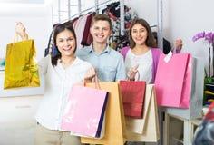 Type et deux filles tenant des sacs Image stock