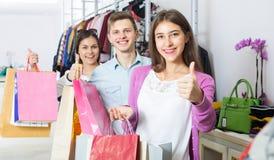 Type et deux filles tenant des sacs Photos stock