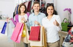 Type et deux filles tenant des sacs Photographie stock libre de droits