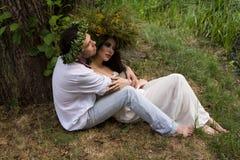 Type et fille avec des guirlandes sur leurs têtes sous l'arbre Photographie stock libre de droits